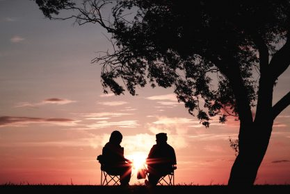 2 people sitting at sunset